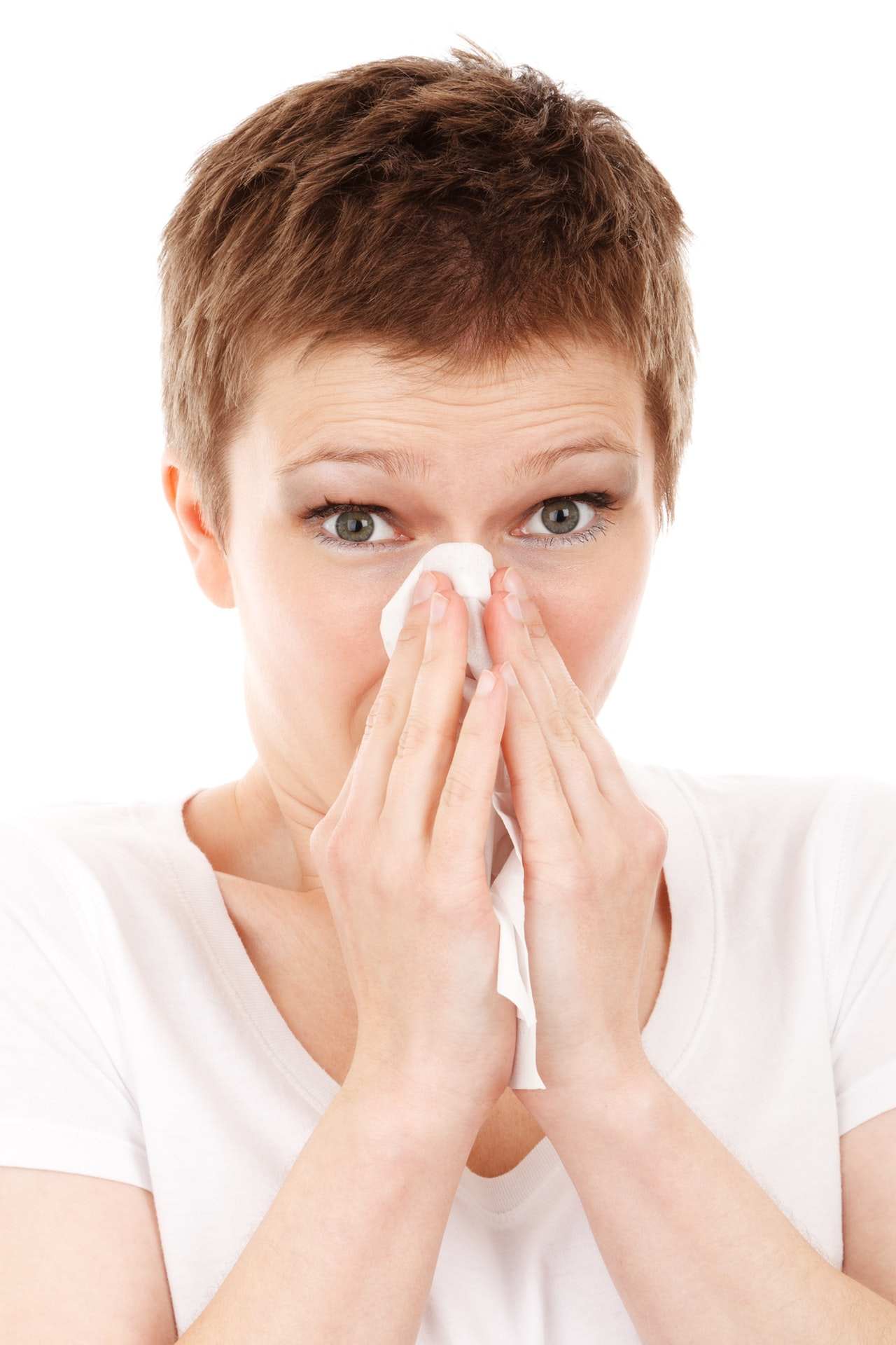 woman blowing her nose, sick due to flu